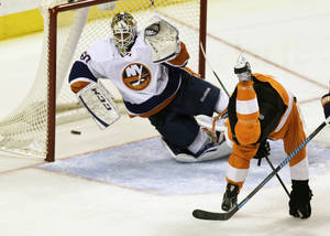 Photo - Philadelphia Flyers' Claude Giroux (not pictured) takes a shot for a goal past New York Islanders' goalie Kevin Poulin as the Flyers' Scott Hatnell (19) tumbles in the second period of an NHL hockey game, Saturday, Nov. 23, 2013, in Philadelphia. (AP Photo/Laurence Kesterson)