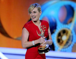 "Photo -   FILE - In this Sept. 18, 2011 file photo, Kate Winslet accepts the award for outstanding lead actress in a mini-series or movie for ""Mildred Pierce"" at the 63rd Primetime Emmy Awards in Los Angeles. The Academy of Television Arts & Sciences said Thursday, May 31, 2012 that it will merge the leading and supporting acting categories for such longform programming. Starting with the 2013 awards, new categories for outstanding actor in a miniseries or TV movie and outstanding actress in a miniseries or movie will each include six nominees. Previously, the four movie and miniseries acting categories included five nominees. (AP Photo/Mark J. Terrill, file)"