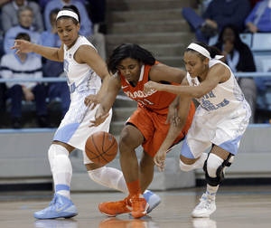 Photo - Syracuse's Cornelia Fondren (11) chases the ball with North Carolina's Latifah Coleman (2) and Allisha Gray, left, during the first half of an NCAA college basketball game in Chapel Hill, N.C., Thursday, Jan. 30, 2014. (AP Photo)