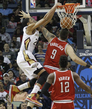 Photo - New Orleans Pelicans forward Anthony Davis (23) dunks over Milwaukee Bucks center Miroslav Raduljica (9) as Bucks forward Jeff Adrien (12) watches during the first half of an NBA basketball game in New Orleans, Friday, March 7, 2014. (AP Photo/Bill Haber)