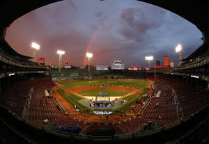Photo - IN this image taken with a fisheye lens, Boston Red Sox players take batting practice as a rainbow appears in the sky above Fenway Park Tuesday, Oct. 22, 2013, in Boston. The Red Sox are scheduled to host the St. Louis Cardinals in Game 1 of baseball's World Series on Wednesday. (AP Photo/Elise Amendola)