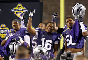 Photo - From left to right, Kansas State's Dante Barnett, Tyler Lockett, and Tre Walker celebrate a win over Michigan after the Buffalo Wild Wings Bowl NCAA college football game Saturday, Dec. 28, 2013, in Tempe, Ariz.  Kansas State defeated Michigan 31-14. (AP Photo/Ross D. Franklin)