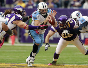 Photo -   Tennessee Titans quarterback Matt Hasselbeck, center, scrambles between Minnesota Vikings defensive end Brian Robison, second from left, and defensive end Jared Allen (69) during the first half of an NFL football game on Sunday, Oct. 7, 2012, in Minneapolis. (AP Photo/Genevieve Ross)