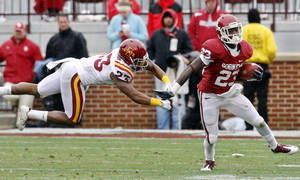 Photo - Oklahoma running back Brandon Williams (23) avoids a flying tackle by Iowa State cornerback Leonard Johnson (23) during the fourth quarter of an NCAA college football game in Norman, Okla., Saturday, Nov. 26, 2011. (AP Photo/Sue Ogrocki) ORG XMIT: OKSO109