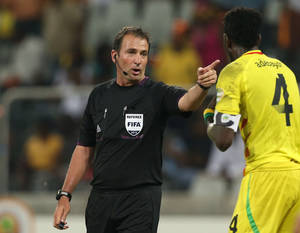 photo - Referee Daniel Bennett of South Africa, left, gestures as Togo's Emmanuel Adebayor, right, appeals for a penalty during their African Cup of Nations Group D soccer match at Mbombela Stadium in Nelspruit, South Africa, Wednesday Jan. 30, 2013. (AP Photo/Themba Hadebe)