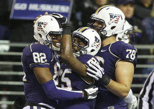 Photo - Washington's Bishop Sankey (25) and Mike Criste (78) greet Joshua Perkins (82) by after Perkins scored a touchdown against Colorado in the first half of an NCAA college football game on Saturday, Nov. 9, 2013, in Seattle. (AP Photo/Ted S. Warren)