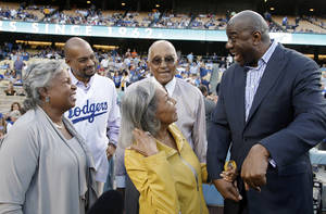 "photo -   Los Angeles Dodgers new co-owner Earvin ""Magic"" Johnson, right, talks with, from left, Jackie Robinson's daughter Sharon Robinson; grandson Jesse Sims; widow, Rachel Robinson; and Dodgers great Don Newcombe at Dodger Stadium, before the Dodgers' baseball game against the San Francisco Giants in Los Angeles on Monday, May 7, 2012. (AP Photo/Reed Saxon)"