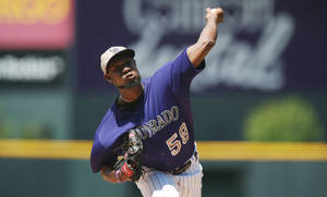 Photo - Colorado Rockies starting pitcher Yohan Flande works against the Los Angeles Dodgers in the first inning of a baseball game in Denver, Sunday, July 6, 2014. (AP Photo/David Zalubowski)