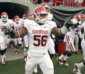 Photo - Ronnell Lewis (56) leads the team onto the field for the college football game between the University of Oklahoma Sooners (OU) and the University of Cincinnati Bearcats (UC) at Paul Brown Stadium on Saturday, Sept. 25, 2010, in Cincinnati, Ohio.   Photo by Steve Sisney, The Oklahoman