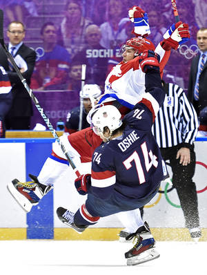 Photo - United States forward  T.J. Oshie (74) is hit by Russia forward Alex Ovechkin, back, during a men's ice hockey game at the 2014 Winter Olympics, Saturday, Feb. 15, 2014, in Sochi, Russia. The U.S. won 3-2 in a shootout. (AP Photo/The Canadian Press, Nathan Denette)