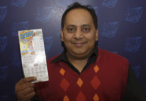 photo - FILE - This undated file photo provided by the Illinois Lottery shows Urooj Khan, of Chicago, posing with a winning lottery ticket. Khan died from cyanide poisoning in July 2012 shortly before collecting $425,000 in winnings. An attorney who represents Khan's widow says most of the businessman's $2 million estate should go to his client, the Chicago Sun-Times reported Thursday, Feb. 7, 2013. (AP Photo/Illinois Lottery, File)