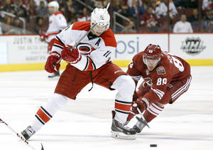 Photo - Carolina Hurricanes' Jordan Staal (11) battles Phoenix Coyotes' Mikkel Boedker (89), of Denmark, for the puck during the first period of an NHL hockey game, Saturday, Dec. 14, 2013, in Glendale, Ariz. (AP Photo/Ross D. Franklin)