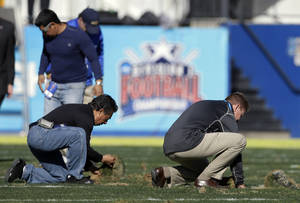 Photo - Stadium staff work on smoothing out the up-turned turf during a time out in play in the first half of the FCS championship NCAA college football game between North Dakota State and Towson, Saturday, Jan. 4, 2014, in Frisco, Texas. (AP Photo/Tony Gutierrez)