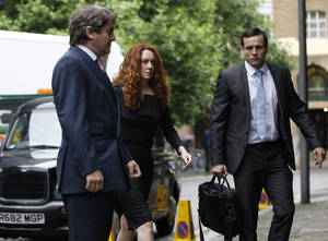 photo -   Former News International chief executive Rebekah Brooks, center, accompanied by her husband Charlie Brooks, left arrives to appear at Southwark Crown court on charges relating to the phone hacking scandal, in London, Friday, June 22, 2012. (AP Photo/Lefteris Pitarakis)