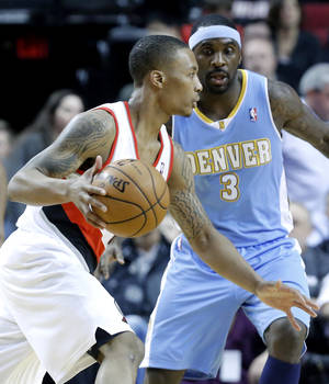 Photo - Portland Trail Blazers guard Damian Lillard, left, drives against Denver Nuggets guard Ty Lawson during the first quarter of an NBA basketball game in Portland, Ore., Thursday, Dec. 20, 2012. (AP Photo/Don Ryan)
