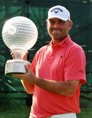 Photo - Denmark's Thomas Bjorn with the trophy after winning the Nedbank Golf Challenge at Sun City South Africa, Sunday, Dec 8, 2013.  (AP Photo)