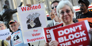 Photo - Demonstrators hold signs during a voter ID rally September 13, 2012 in Philadelphia, Pennsylvania. The Pennsylvania Supreme Court held a hearing on Pennsylvania's state Supreme Court justices on whether a law requiring photo identification from each voter should take effect for the Nov. 6 presidential election. (William Thomas Cain/MCT via Getty Images)