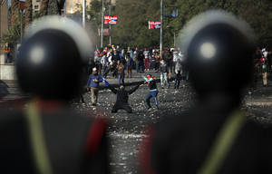 Photo - Egyptian protesters clash with riot police near Tahrir Square, Cairo, Egypt, Tuesday, Jan. 29, 2013. Intense fighting for days around central Tahrir Square engulfed two landmark hotels and forced the U.S. Embassy to suspend public services on Tuesday. (AP Photo/Khalil Hamra)