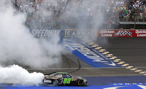 Photo - Dale Earnhardt Jr., celebrates with a burnout after winning the Quicken Loans 400 at Michigan International Speedway on Sunday in Brooklyn, Mich. AP Photo