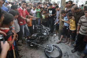 "Photo -   Palestinians gather a round the wreckage of motorcycle following an Israeli air strike in Rafah, southern Gaza Strip, Sunday, Oct. 7, 2012. Israel's military says it has fired on two Gaza members of an al-Qaida-inspired group identified as having been involved in rocket attacks and an infiltration from Egypt. Palestinians say one man was killed. The military said they were involved in ""extensive terrorist activity,"" including an attack in June where two gunmen crossed into Israel from the Sinai desert and killed a civilian. Israel did not say whether it hit the two. Ashraf al-Kidra, a Palestinian health official in Gaza said one man was killed and another injured Sunday when their motorcycle was hit by aircraft in the south of the Hamas-controlled territory. Israel and Hamas have mostly kept an unwritten truce since a short war over three years ago. Attacks have persisted but at a much lower rate. (AP Photo/Eyad Baba)"