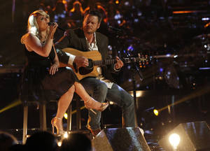 This May 21, 2013 photo released by NBC shows married singers Miranda Lambert, left, and  Blake Shelton performing an acoustic version of the hit Over You during a broadcast of the singing competition series, The Voice, in Los Angeles. Shelton and NBC are putting together a benefit for Oklahoma tornado victims. Shelton, an Oklahoma native, told reporters about the fundraising effort after Tuesday night's episode of The Voice. He said the benefit would be held soon in nearby Oklahoma City.  (AP Photo/NBC, Trae Patton)