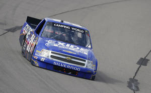Photo - James Buescher races his car during the NASCAR Truck Series auto race, Sunday, Sept. 8, 2013, at Iowa Speedway in Newton, Iowa. (AP Photo/Charlie Neibergall)