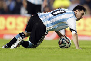 Photo - Argentina's Lionel Messi gets up during an international friendly soccer match with Slovenia in La Plata, Argentina, Saturday, June 7, 2014. Argentina's team is leaving June 9 for Brazil to compete in the World Cup. (AP Photo/Natacha Pisarenko)