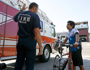 photo - Fire Cpl. Doug Wright shows Joseph Machado, 13, fire equipment Wednesday. Machado is riding his bike across America to raise money for charity and stayed with the fire department while in Oklahoma City.  PHOTOS by Mitchell Alcala, The Oklahoman