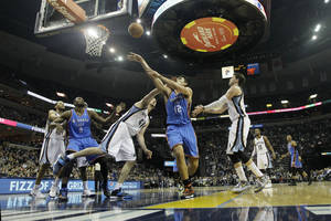 Photo - Oklahoma City Thunder's Steven Adams (12), of New Zealand, shoots over Memphis Grizzlies' Kosta Koufos (41) in the first half of an NBA basketball game in Memphis, Tenn., Wednesday, Dec. 11, 2013. (AP Photo/Danny Johnston)