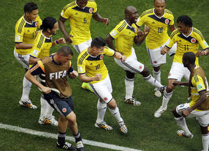 Photo - FILE - In this June 19, 2014, file photo, Colombia's James Rodriguez, center, dances with teammates in celebration after scoring during the group C World Cup soccer match between Colombia and Ivory Coast at the Estadio Nacional in Brasilia, Brazil. The euphoria in soccer-mad Colombia is deafening, and wonderfully contagious, ahead of Friday's do-or-die World Cup match against host Brazil. Not since Colombia drubbed Argentina 5-0 in a 1993 World Cup qualifier has the South American nation of 48 million been so enthralled by the beautiful game. (AP Photo/Themba Hadebe, File)