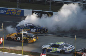 Photo - Sprint Cup Series driver Martin Truex Jr. (56) spins out as Marcos Ambrose (9) and Casey Mears (13) pass by during the NASCAR Sprint Cup  auto race at Martinsville Speedway in Martinsville, Va., Sunday, Oct. 27, 2013. (AP Photo/Steve Sheppard)