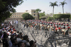 Photo -   Protesters and security forces are separated by barbed wire in Cairo, Egypt. Nearly a dozen people were killed in clashes that broke out Wednesday when apparent supporters of the ruling military council attacked a mostly Islamist crowd staging a sit-in outside the Ministry of Defense in Cairo to call for an end to the generals' rule/ (AP Photo/Mohammed Asad)