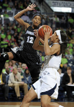 photo - Notre Dame guard Skylar Diggins, right, scores her 2,000th career point as Providence guard Symone Roberts defends in the first half of an NCAA college basketball game, Saturday, Jan. 26, 2013, in South Bend, Ind. (AP Photo/Joe Raymond)
