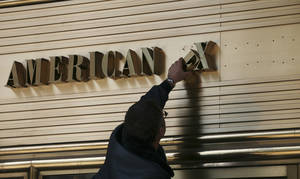 Photo - FILE - In this April 3, 2008 file photo, a worker replaces letters on the American Express sign at the financial services company world headquarters building in New York. American Express Co. reports quarterly financial results after the market closes on Thursday, Jan. 16, 2013. (AP Photo/Mark Lennihan, File)