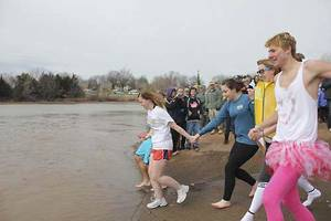 Photo - Volunteers head for the frigid water during the 2012 Polar Plunge at Stillwater's Boomer Lake. PHOTO PROVIDED