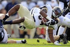 Photo -   Navy fullback Noah Copeland (34) is stopped by Penn State linebackers Mike Hull, left, and Michael Mauti, right rear, during the second quarter of an NCAA college football game in State College, Pa., Saturday, Sept. 15, 2012. (AP Photo/Gene J. Puskar)