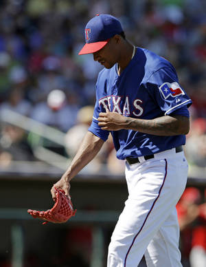 Photo - Texas Rangers starting pitcher Alexi Ogando walks to the dugout after being taken out of the game during the fourth inning of a spring exhibition baseball game against the Los Angeles Angels, Wednesday, March 12, 2014, in Surprise, Ariz. (AP Photo/Darron Cummings)