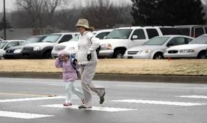 Photo - Katherine Ronck and Anna Ronck, 5, run across the cross walk at Chisholm Elementary  School, Tuesday, Dec. 9, 2008, in Edmond, Okla. STAFF PHOTO BY SARAH PHIPPS