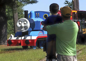 Photo - In this 2012 photo provided by Edaville USA, a father and son watch Thomas the Tank Engine roll down the track at an annual Day Out with Thomas event at the Edaville USA theme park in Carver, Mass. Groundbreaking for the first permanent Thomas Land in the the United States is set for July 2014 at Edaville USA, and is expected to be open for business in the summer of 2015. (AP Photo/Edaville USA)