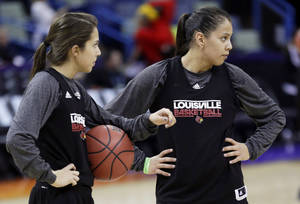 Photo - Louisville's Jude Schimmel, left, and her sister Shoni Schimmel warm up during practice at the Women's Final Four of the NCAA college basketball tournament, Saturday, April 6, 2013, in New Orleans. Louisville plays California in a semifinal game on Sunday. (AP Photo/Gerald Herbert)