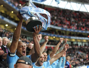 Photo - Manchester City captain Vincent Kompany lifts the English League Cup trophy after defeating Sunderland in the final at Wembley Stadium, London Sunday March 2, 2014. City won the match 3-1. (AP Photo/Adam Davy/Pool)