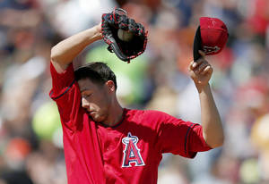 Photo - Los Angeles Angels' Tyler Skaggs wipes his face during the second inning of a spring training baseball game against the San Francisco Giants on Monday, March 24, 2014, in Tempe, Ariz. (AP Photo/Ross D. Franklin)