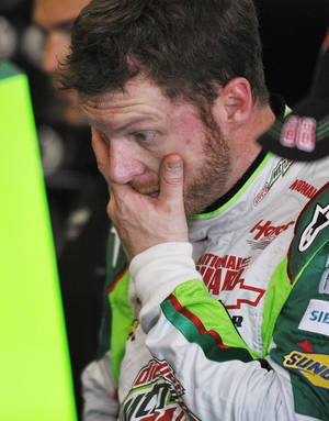 Photo -   NASCAR driver Dale Earnhardt Jr., watches as crew members work on his car in the garage at Talladega Superspeedway in Talladega, Ala., Friday, Oct. 5, 2012. The drivers are preparing for Sunday's running of the NASCAR Sprint Cup Series auto race. (AP Photo/Rainier Ehrhardt)