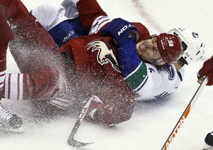 Photo - Phoenix Coyotes' Antoine Vermette (50) gets taken down by Vancouver Canucks' Keith Ballard during the second period in an NHL hockey game, Thursday, March 21, 2013, in Glendale, Ariz. (AP Photo/Ross D. Franklin)