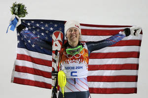 Photo - Women's slalom gold medal winner Mikaela Shiffrin of the United States poses for photographers with the American flag at the Sochi 2014 Winter Olympics, Friday, Feb. 21, 2014, in Krasnaya Polyana, Russia.(AP Photo/Christophe Ena)