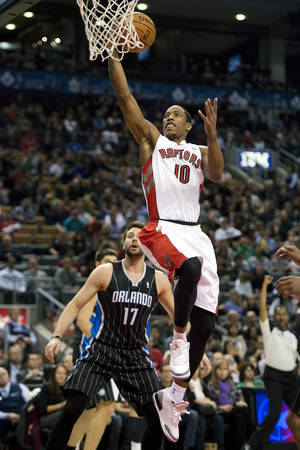 Photo -   Toronto Raptors guard DeMar DeRozan (10) drives to the basket against Orlando Magic forward Josh McRoberts (17) during the first half of an NBA basketball game in Toronto, Sunday, Nov. 18, 2012. (AP Photo/The Canadian Press, Frank Gunn)