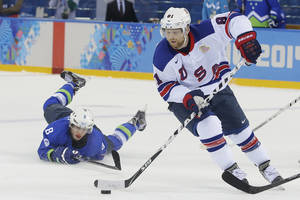 Photo - USA forward Phil Kessel take the puck away from Slovenia forward Ziga Jeglic during the 2014 Winter Olympics men's ice hockey game at Shayba Arena Sunday, Feb. 16, 2014, in Sochi, Russia. (AP Photo/Matt Slocum)