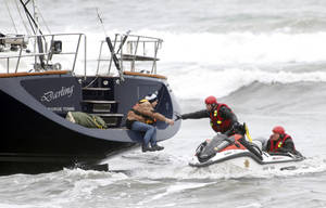 Photo - Rescuers attempt to grab a woman off the back of the 82-foot-long sailboat, the Darling, stuck in the surf off Pacifica, Calif., Monday March 4, 2013. Three people were arrested Monday after they stocked a stolen yacht with pizza and beer, and then ran the vessel aground on a Northern California beach, authorities said. The boat was stolen from Sausalito, Calif. (AP Photo/Bay Area News Group, Karl Mondon)