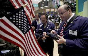Photo - Traders Stephen Kaplan, center, and Jeffrey Vazquez, right, work on the floor of the New York Stock Exchange.  AP Photo
