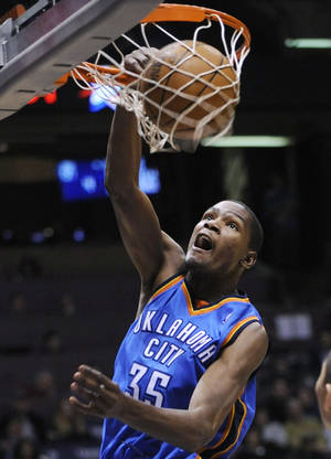 Photo - Oklahoma City Thunder forward Kevin Durant dunks during the fourth quarter of an NBA basketball game against the New Jersey Nets on Monday, Dec. 28, 2009, in East Rutherford, N.J. Durant led all scorers with 40 points as the Thunder beat the Nets 105-89. (AP Photo/Bill Kostroun)